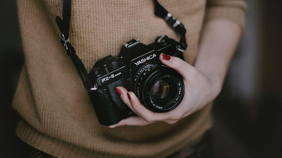 Mulher segurando máquina fotográfica